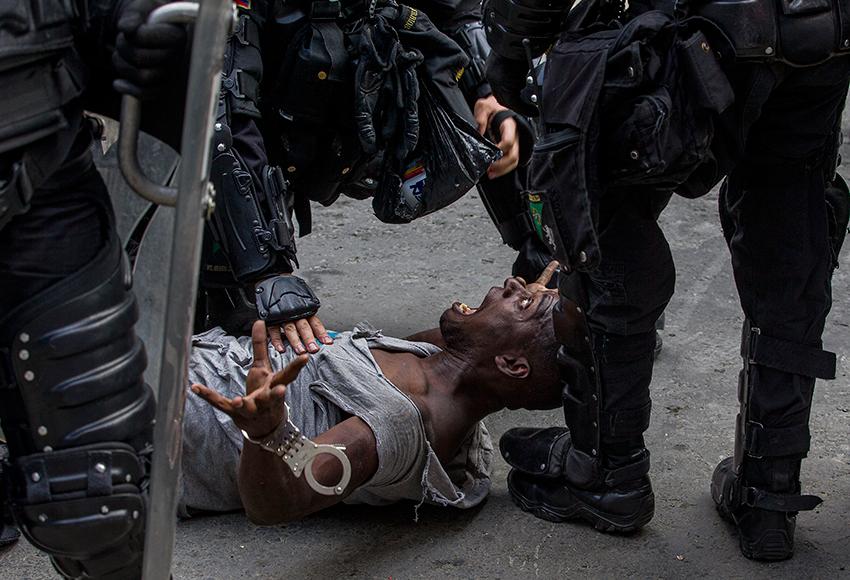 На снимке колумбийца Сантьяго Меса показан арест одного из протестующих во время демонстрации в городе Медельин.