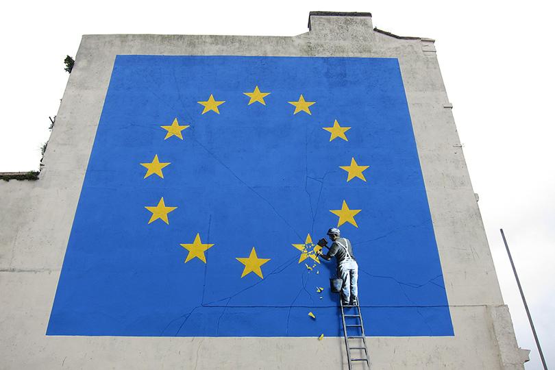 Неугомонный Бэнкси нарисовал нафасаде здания вбританском Дувре флаг Евросоюза с11звездами: 12-ю британскую звездочку награффити бесчувственно отколупывает рабочий