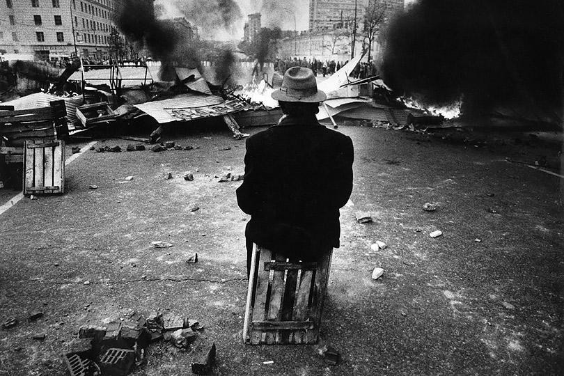 Эдди Опп. Старик сидит наящике перед горящей баррикадой вовремя октябрьских событий 1993 года— попытки государственного переворота, расстрела здания